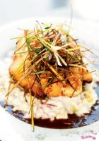 <p>A heavenly parmesan crust pays tribute to snapper lying on a bed of ham and pineapple infused risotto and a pool of port wine reduction. Opposite page: The pimento cheese cake appetizer.</p>