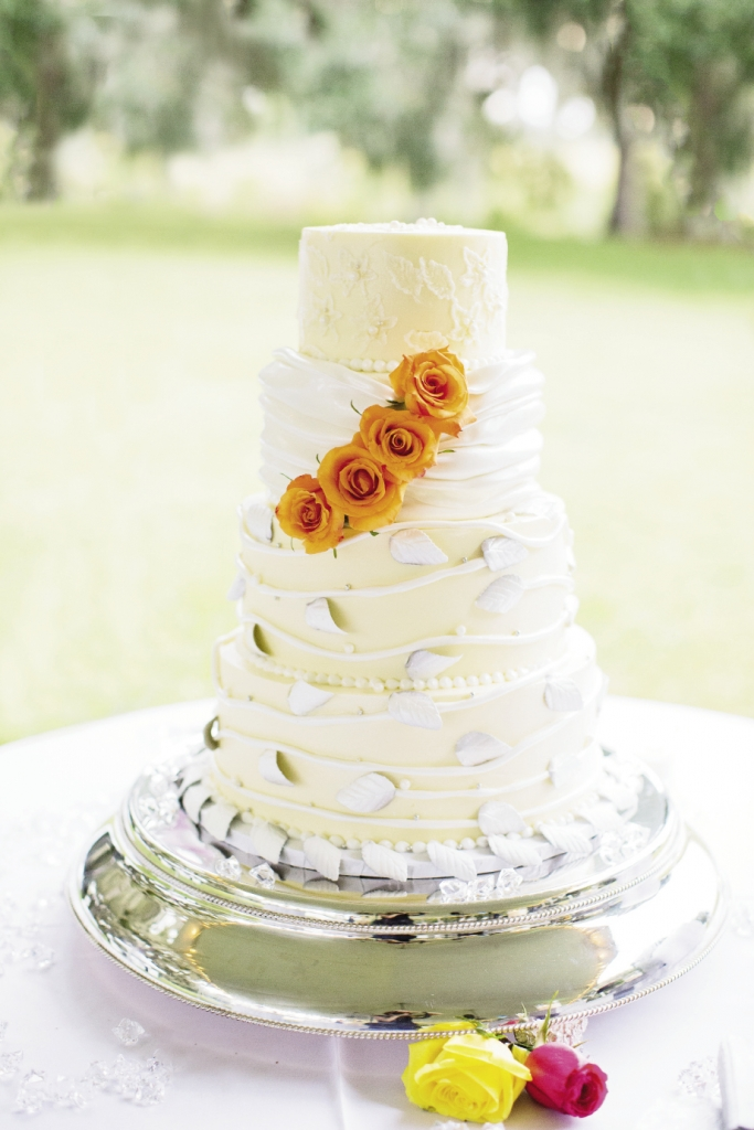 A POP OF ORANGE: Fondant embroidery to match the bride's dress with pearls and silver bead accents is what Denise Johnson had in mind when she designed her wedding cake with Croissants Bistro & Bakery. For Denise's wedding to Buster Farley, they chose a vanilla cake with chocolate raspberry filling.