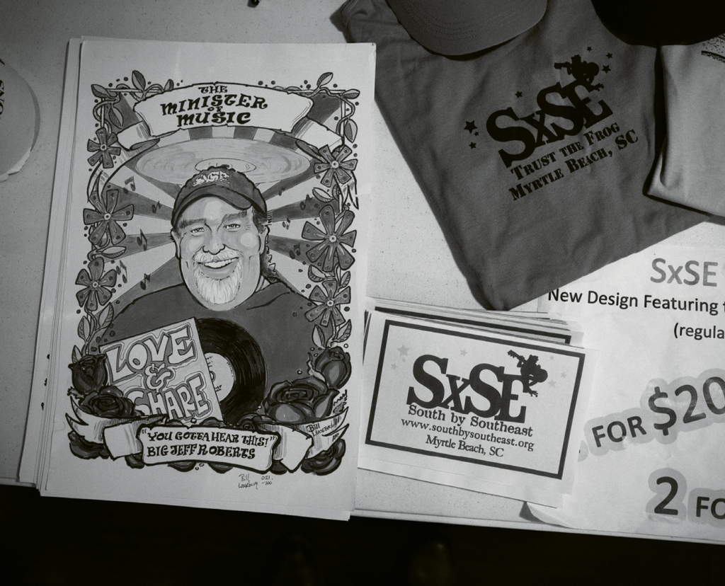 "SXSE swag for sale during the Randall Bramblett show. Pictured is a poster of the late Jeff Roberts, nicknamed ""The Minister of Music"" by his close friends. Roberts was one of the founders of the series and his memory is honored with a toast before each show."