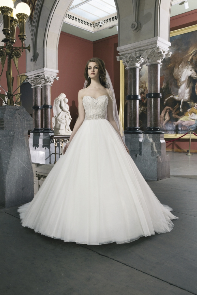 JUSTIN ALEXANDER: This tulle ballgown features an intricately beaded bodice with a sweetheart neckline and regal satin buttons down the zipper. Style 8724. The Little White Dress, $1,658