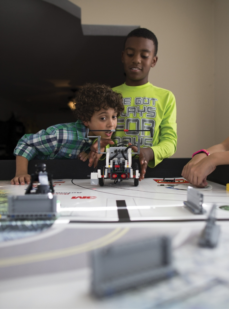 The First LEGO League is all about the fun of learning S.T.E.M. (Science, Technology, Engineering, Math). Here, Trent Toole and Jayden Johnson prepare to launch their robot on the game board.
