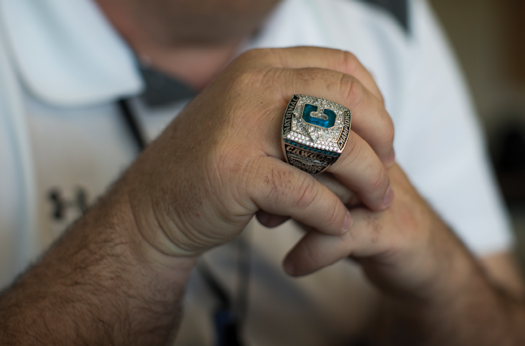 Assistant Athletics Director Mike Cawood wears his CCU championship ring while watching pre-game activities from the press box