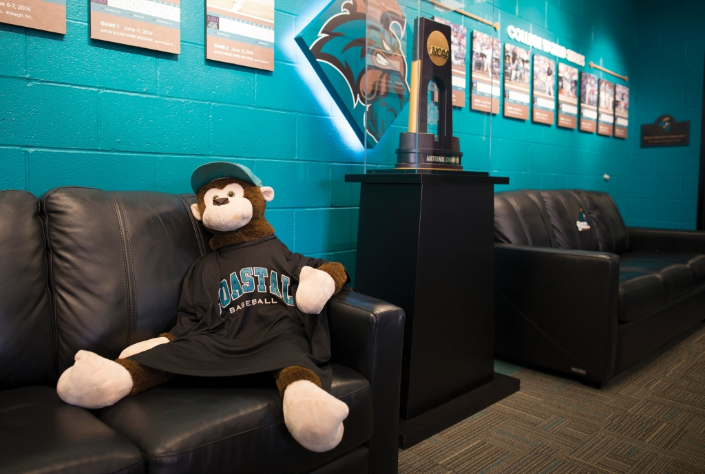 Rafiki relaxes in the clubhouse with the College World Series trophy.