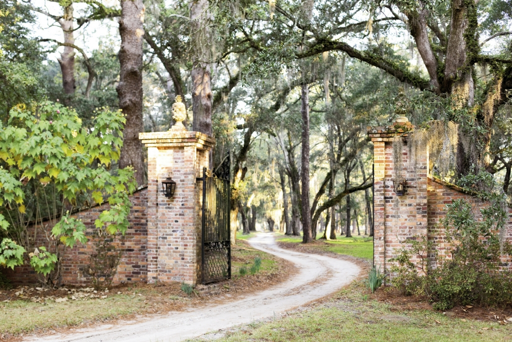 The long and winding road to Estherville Plantation starts at these lighted brick pillars supporting pineapple finials, the Sout