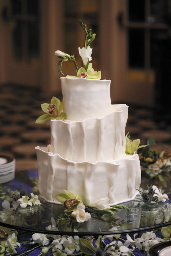 The Cake: Incredible Edibles' Myra Ranta took inspiration for this cake from the unusual ruffling on the bodice, which was the bride's favorite part of the dress. The cake was frosted in buttercream, then a hand-ruffled fondant was carefully applied to the sides.