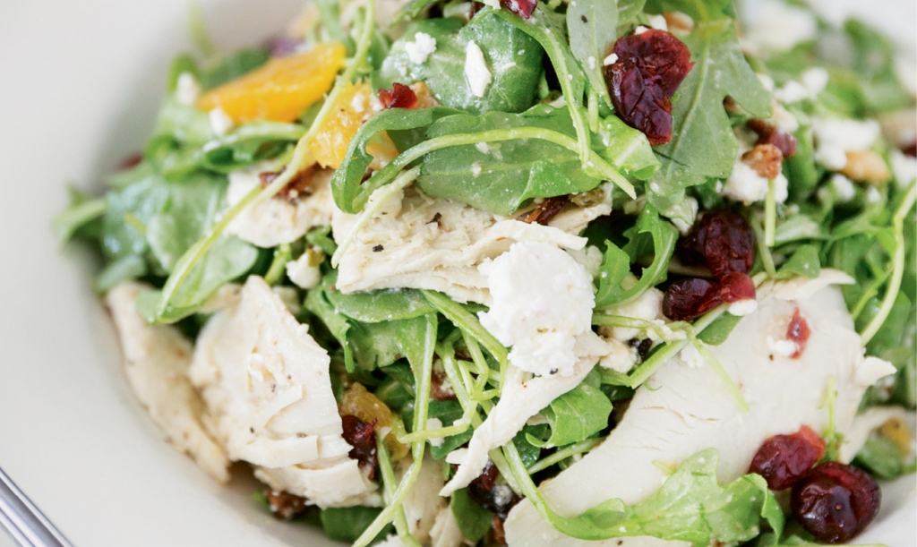 The Grilled Chicken Arugula Salad gets sweetened up with tangy dried cranberries, pecans and orange wedges.