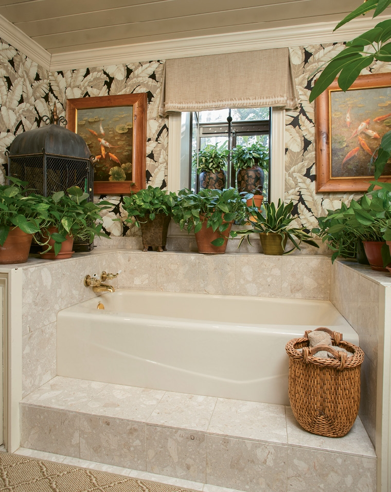 A soaking tub communes with the natural elements of live plants and parakeets