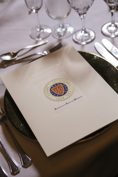 The Table Is Set: A formal program at each place setting introduces the guests for the evening and gives details of each food course and wine to be served. At right, middle photo, from left: Chaîne Officier Bonnie Fisher (with ribbon),Chevalier Rick Fallon, Dame de la Chaîne Sharon Fallon.