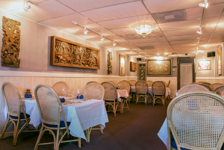 The cozy dining room at Blue Elephant is a white linen affair with beautiful dishware.
