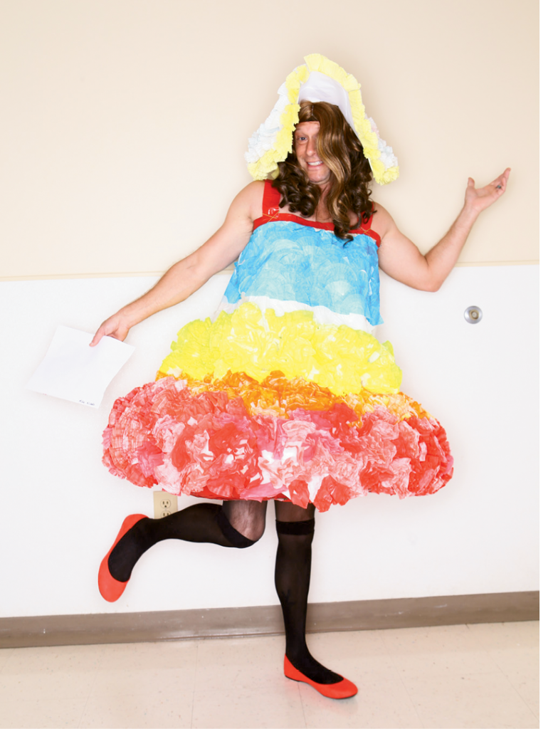 """Most Humorous  Designers: Carol Deese, Kathy Falvey, Keisha Johnson and Alexander Taylor representing Blue Cross Blue Shield  Sponsoring Company: BCBSSC Deese and Co.  Model: Michael Nichols  Description of outfit: The name of this design is """"Colors of Sunrise."""" The materials used include cupcake liners, coffee filters, swimming pool ring, duct tape, hot glue, playing cards and paper."""