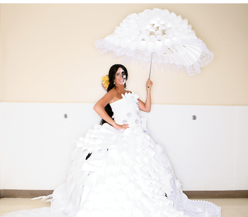 "Most Creative Award  Designers: Southern Belles of Miller-Motte Technical College  Sponsoring company: Miller-Motte Technical College  Model: Christina Capo  Description of outfit: The name of this fashion is ""Dia de los muertos wedding dress."" Materials used include paper; Styrofoam cups, plates and bowls; plastic forks and spoons; lace; pop tabs; metal wire; tissue paper; doilies; plastic wrap; twine and hot glue."