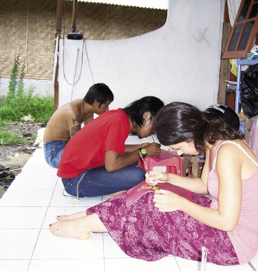 Mehera working alongside staff in Bali, and-detailing a pair of boots.