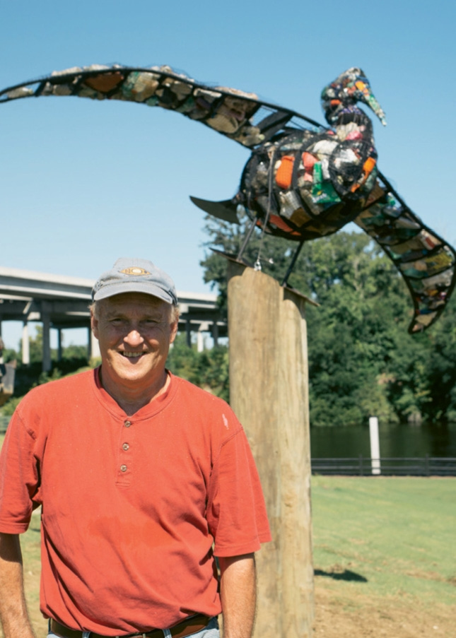 Jim Swaim, pictured here with his Environmental Sculptures artwork that also serve as trash containers.