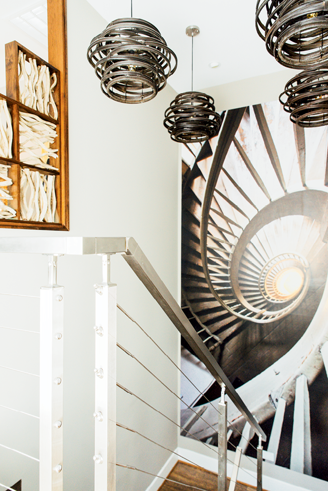 The stunning floating stairway features a wall photo from the inside of a lighthouse and bentwood light fixtures.