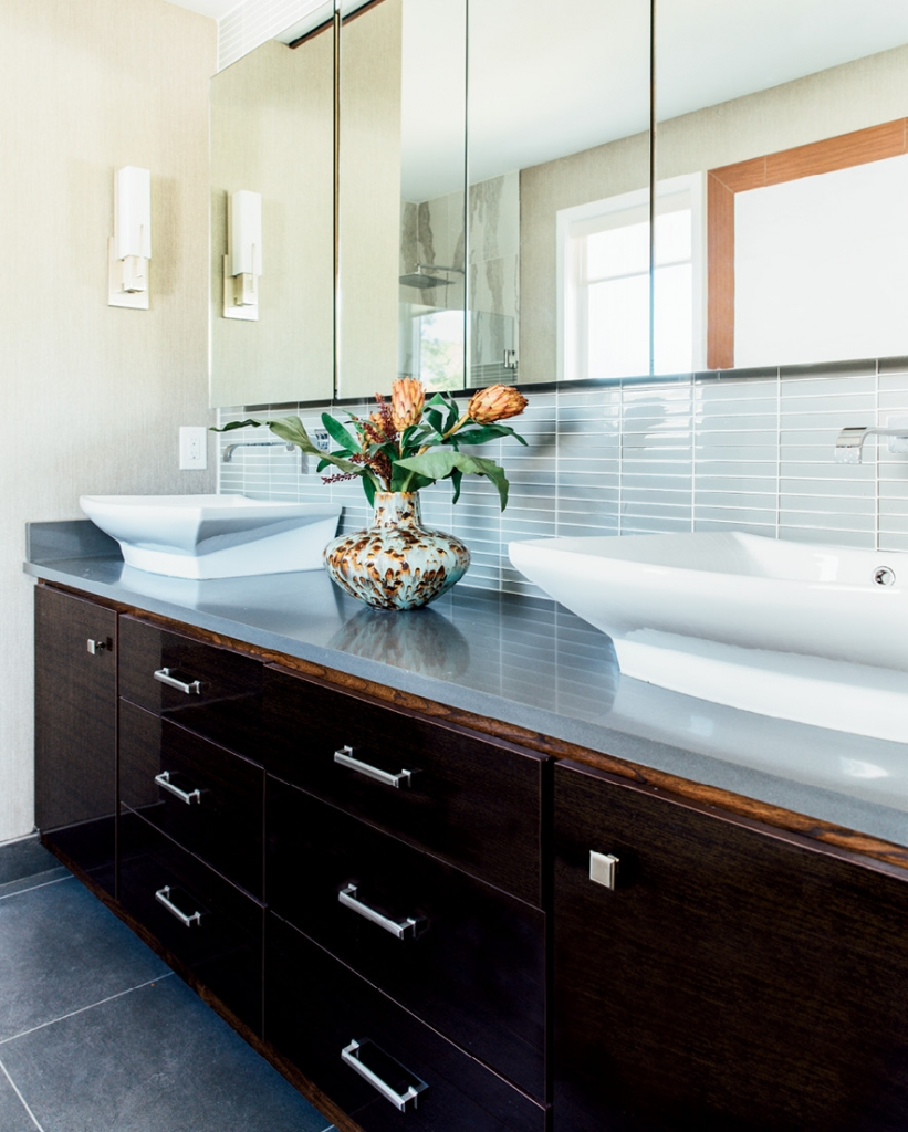 Every bathroom in the Warren house is a work of art. Gleaming wood, mix-and-match tile work and glossy white in cabinets and vessel sinks make these private spaces smart and sleek.