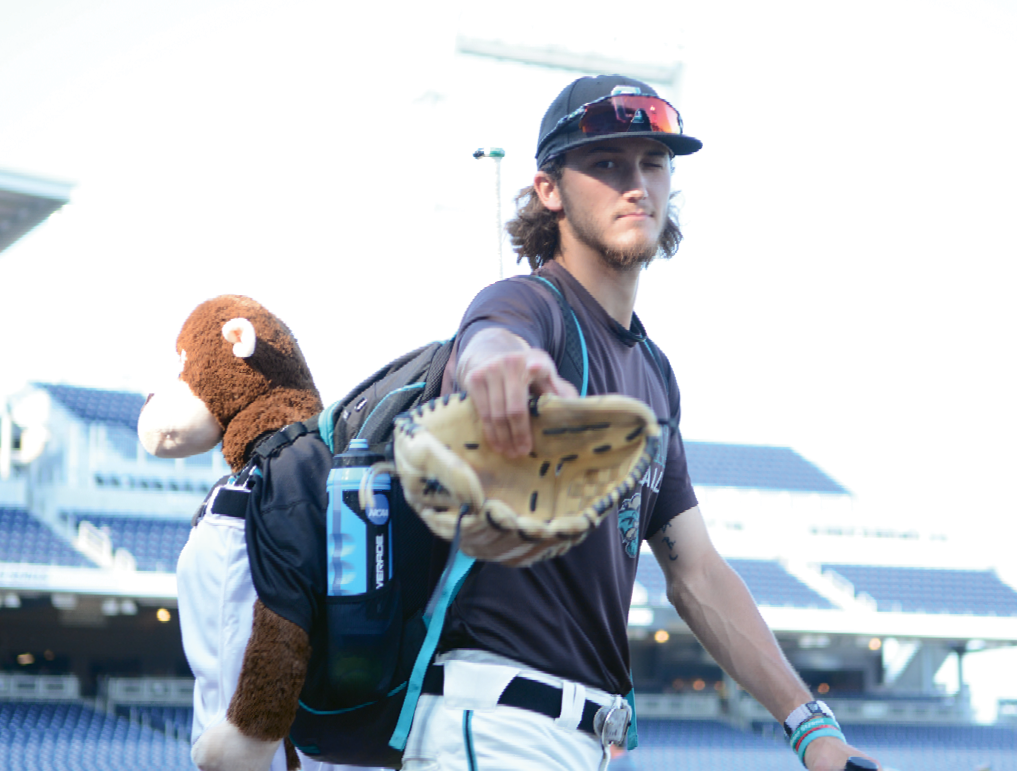 Scenes from the 2016 College World Series: Bobby Holmes takes the field with Rafiki in tow.