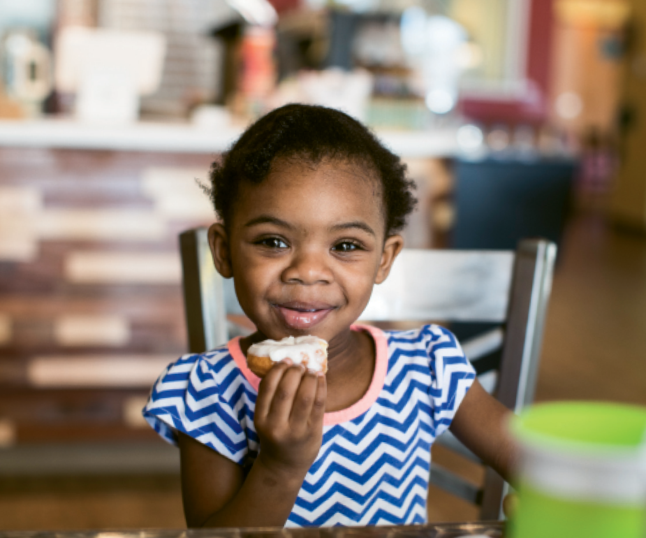 Two-year-old Kaiya Ramsay of Myrtle Beach enjoys a donut at Peace Love and Little Donuts.