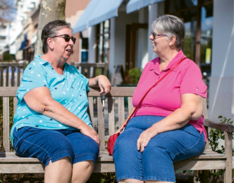 Carol Hannon (left) and her sister, Vivian, talk outside of their Market Common apartment.