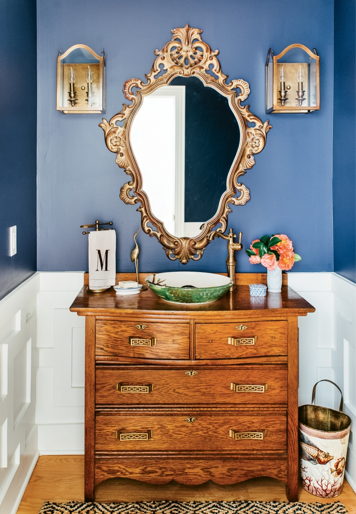 All the right moves were made in this stunning bathroom with Chippendale wainscoting, an antique vanity chest and a hand-painted vessel sink.