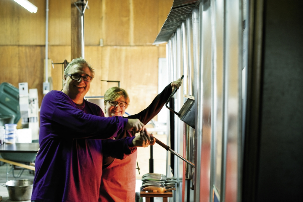"Barbara and Ed Streeter, the ""hot shop team,"" prepare to remove glass from the oven."