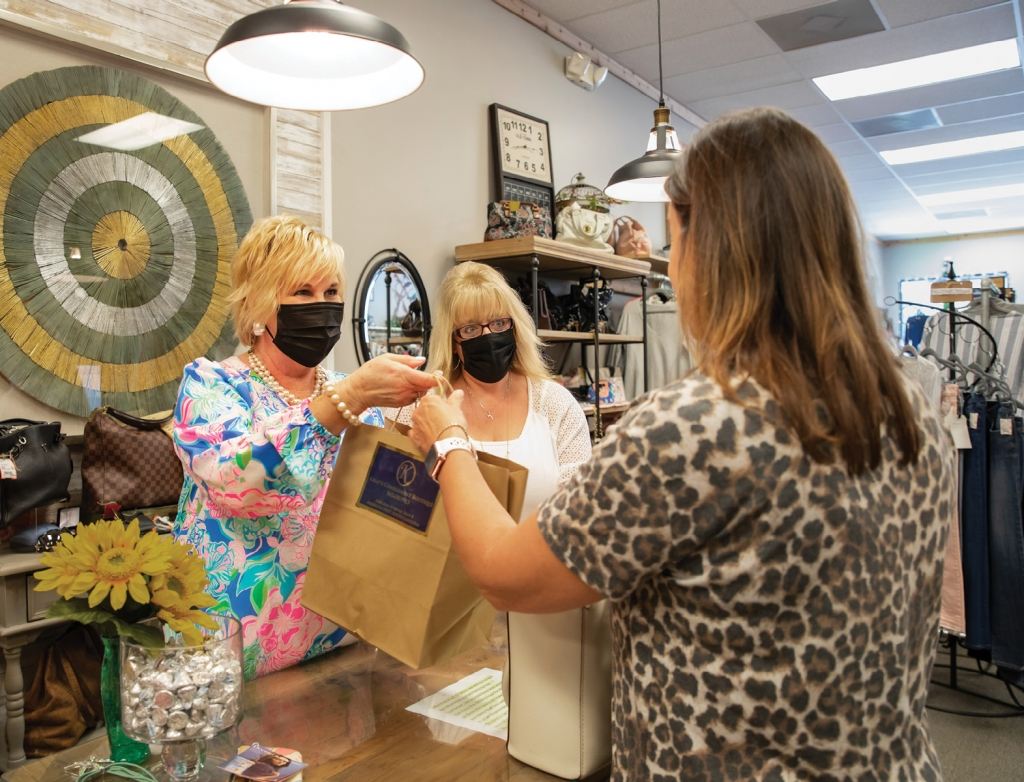 Canipe and Ellie Fischer, middle, assist a customer at Kelly's Consignment Boutique.