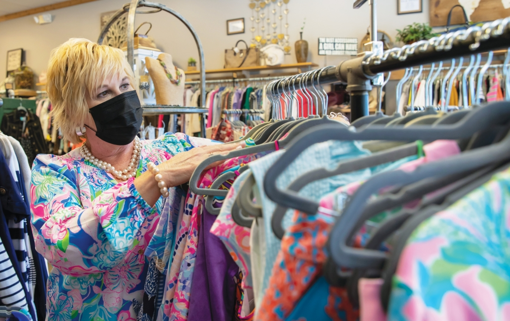 Owner Kelly Canipe straightens the racks at Kelly's Consignment Boutique in Murrells Inlet.