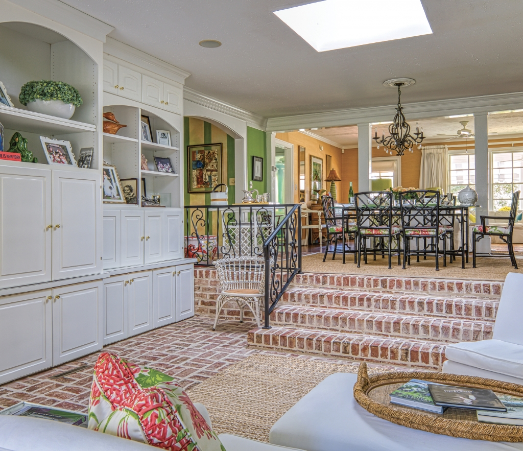 The DeBerry cottage interior reflects elements of outdoor living, with pops of green, florals and brick patio flooring.