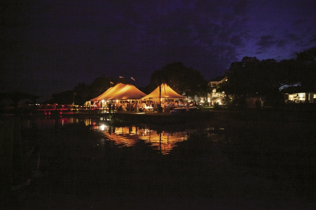 Waterfront Wonders: One of Caroline's fondest wedding memories was the view of the glowing reception tent made of sailboat masts from the couple's pontoon boat departure.