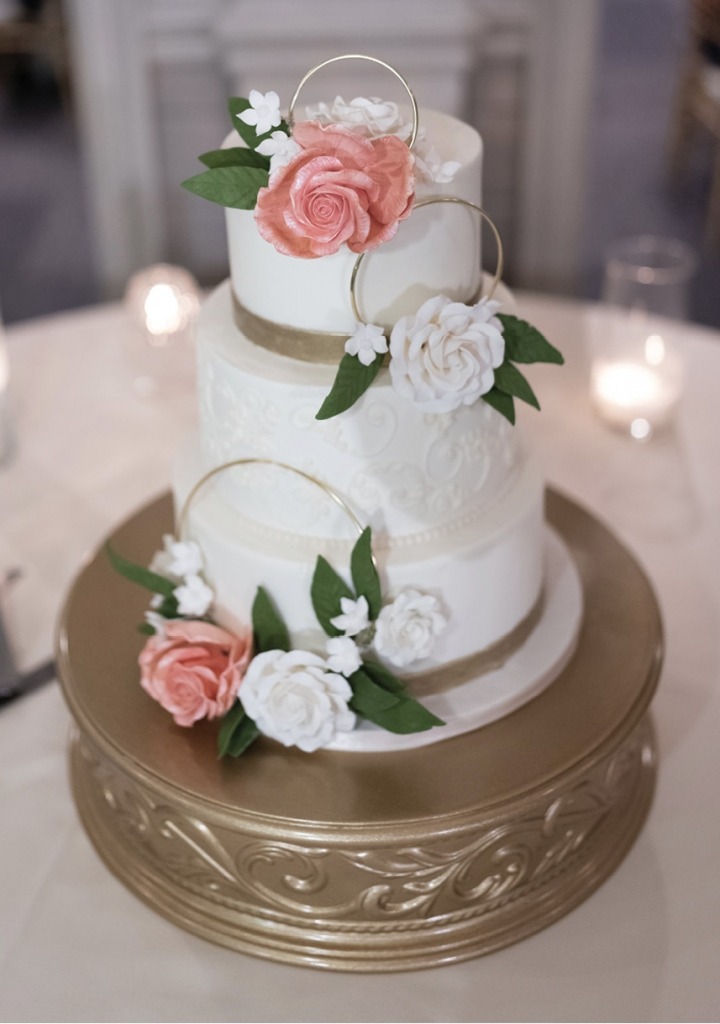 The pretty white cake adorned with gold and flowers was created by Incredible Edibles.