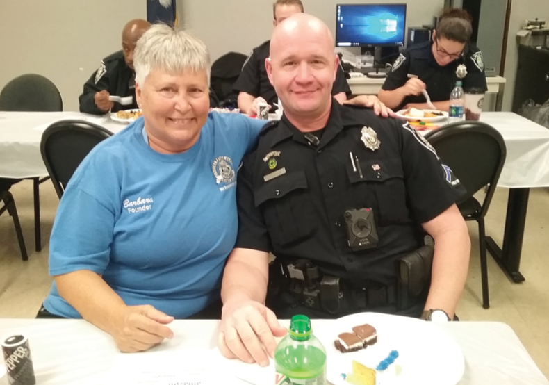 Prescop sits with Myrtle Beach police officer PFC Michael Lee during one of the holiday feasts she organizes for officers.