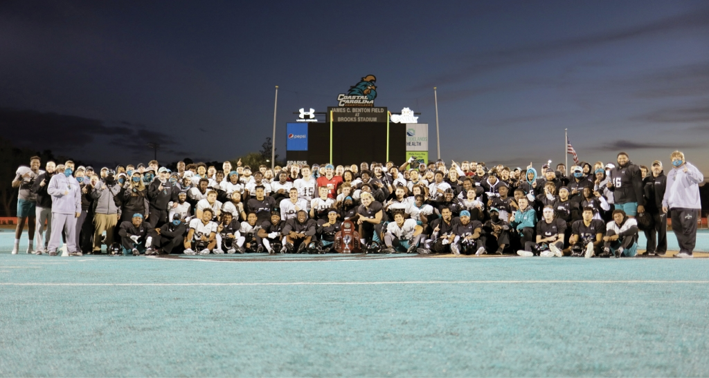 The CCU Chanticleer football conference championship-winning team poses with its trophy.