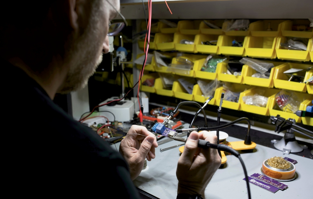 Stewart sits at Subproto's electronic workbench, where he and  members prototype electronic products.