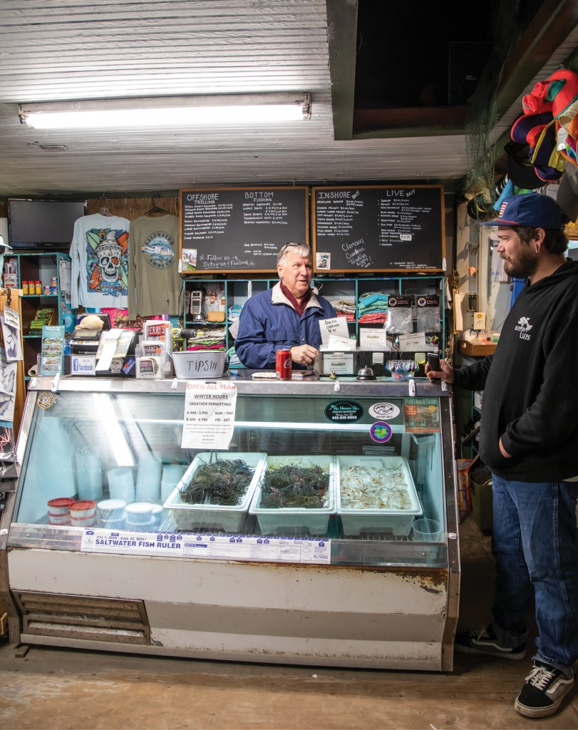 A BIT OF BAIT: Craig, Jessica's father, and Jordan, a Perry's employee, talk shop, surrounded by tanks and fridges of live and chilled bait—some of the most live bait carried in a shop in the area.