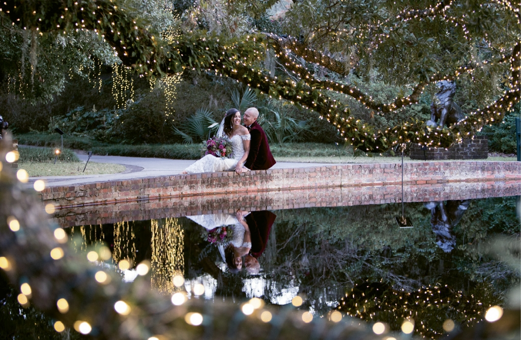 """The lights of Nights of a Thousand Candles created a unique backdrop for this big day. The pair said """"I do"""" at the Live Oak Allee and were married by Anna-Marie's godfather and Adam's friend."""
