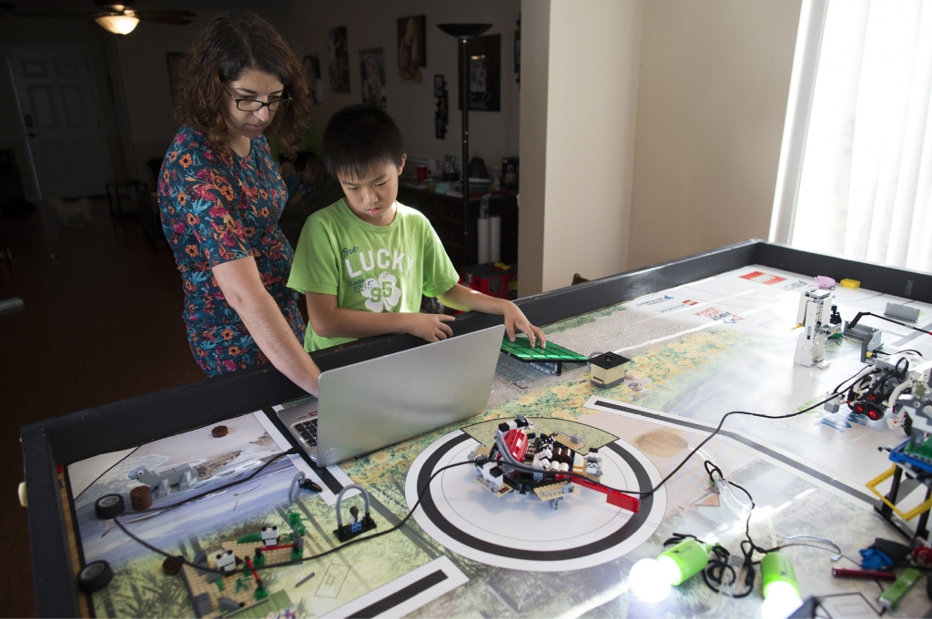 "Brandy Incorvia, the team coach for the ""New Kids on the Bots,"" shows Alan Bao how to adjust the robot's programming on the team's laptop. The drop-and-drag program allows kids to learn coding at an early age. But the team must also step away from the computer and look at the program effects."