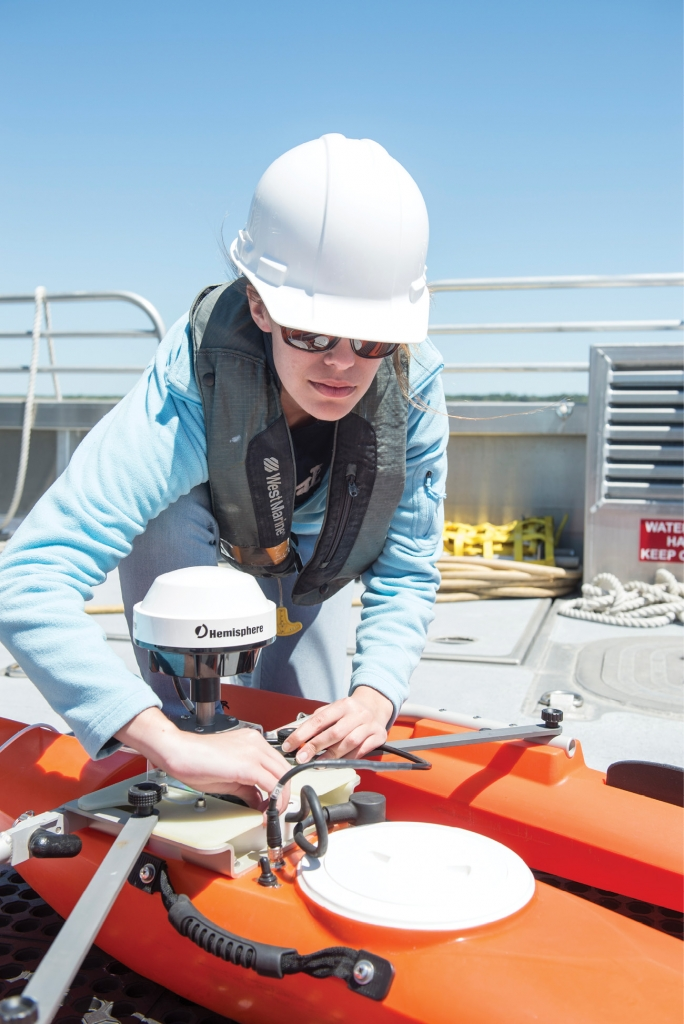 Preparing to Launch: A student prepares to launch a remote-controlled robotic instrument from the deck of CCU's Coastal Explorer.