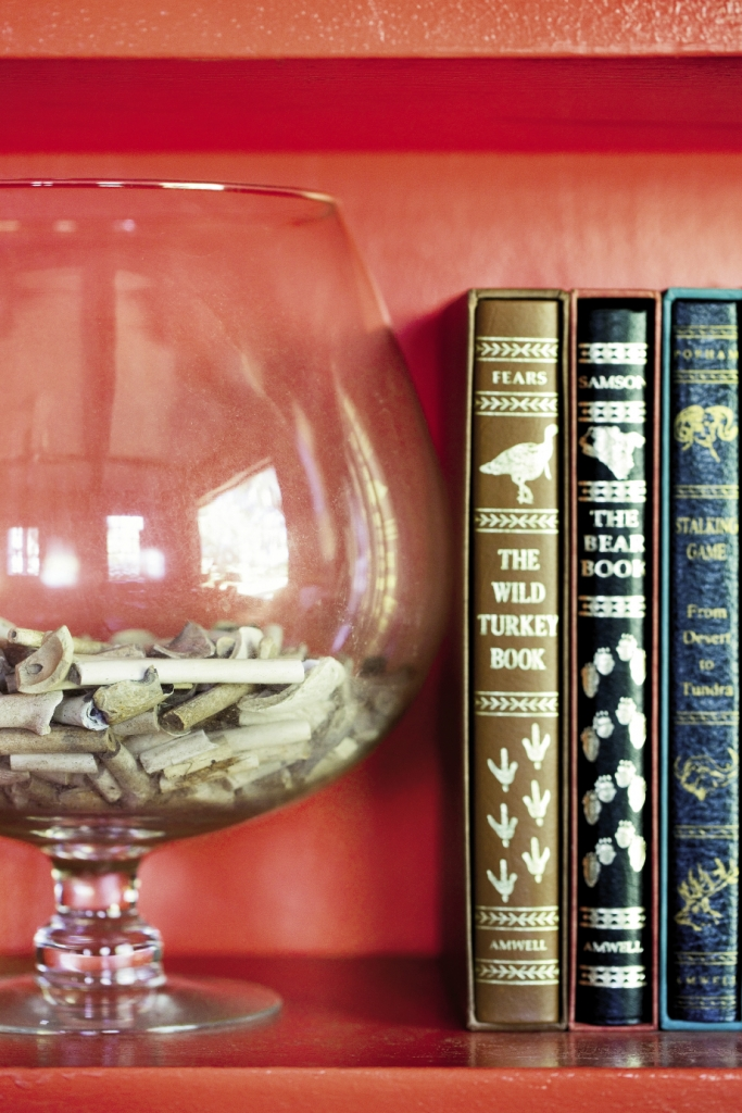 The vermillion painted bookshelves in the study hold a host of historic treasures, like this glass snifter full of pipe stems fr