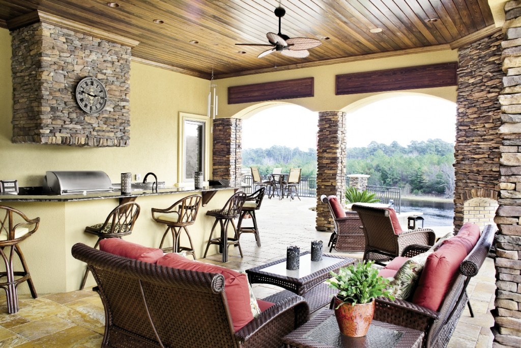 The outdoor kitchen and lounge is accented by stacked faux stonework.