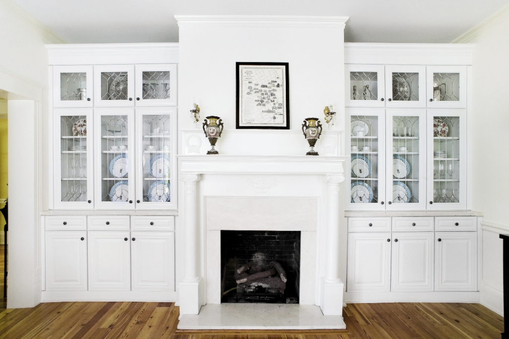 The original fireplace and sconces in the formal dining room mingle seamlessly with new built-in cabinets.