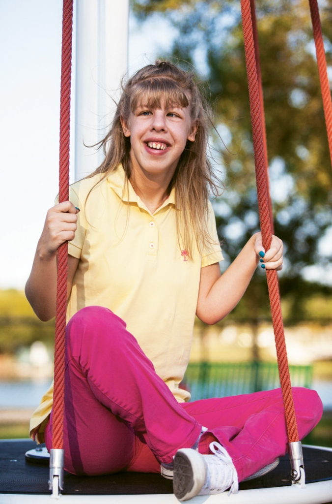 Savannah Thompson is pictured here at the ADA-approved playground that bears her name.