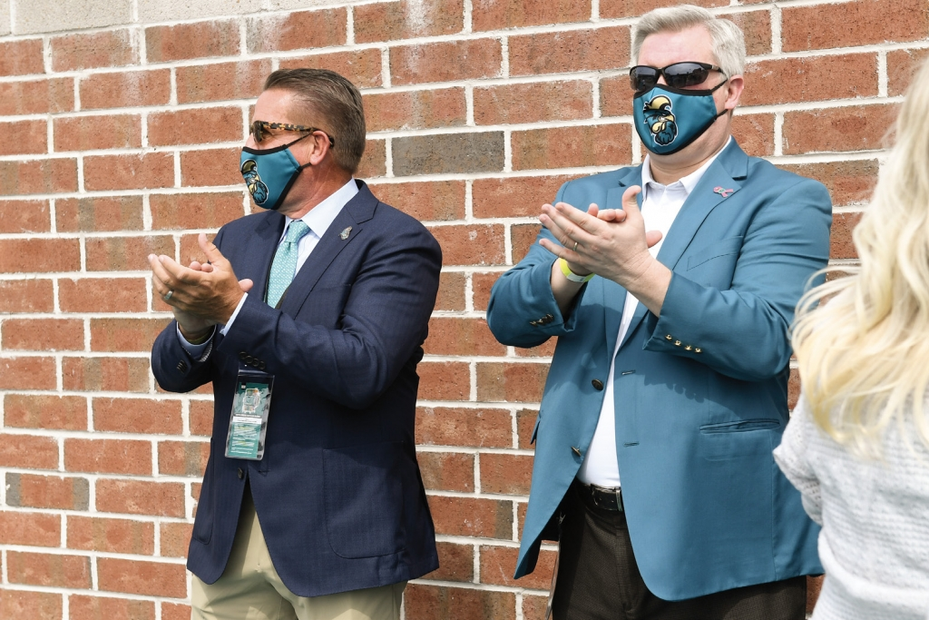New CCU President Dr. Michael Benson (left) cheers the Chanticleers with AD Matt Hogue.