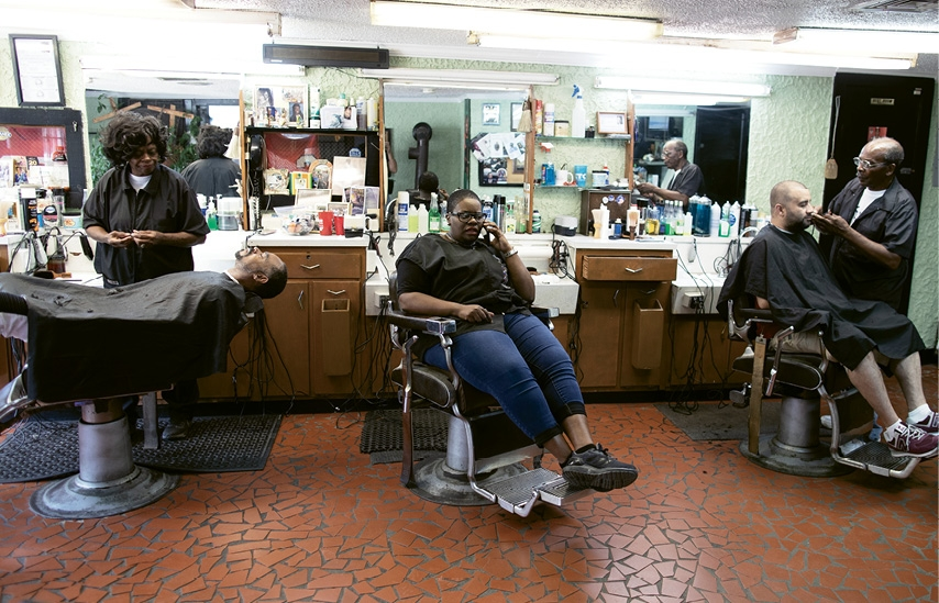 As her mom and Franklin Tucker work on patrons, Portia Thomas, a 42-year-old case manager and part-time barber, makes a quick call.