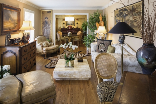 Eclectic At Its Best: The formal living/dining area features a design mashup of an antique chest, zebra skin rug, 1960s marble coffee table and gold leaf cork-covered walls in the dining room.