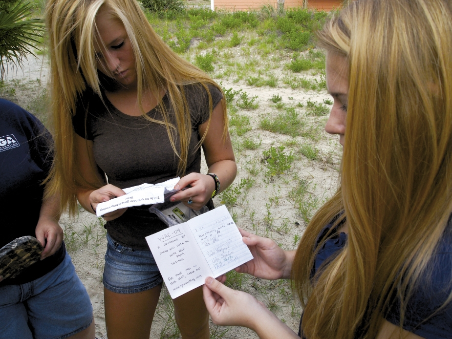 Two of the Schoonover girls read notes left by previous geocachers—some from international visitors who were here on vacation.