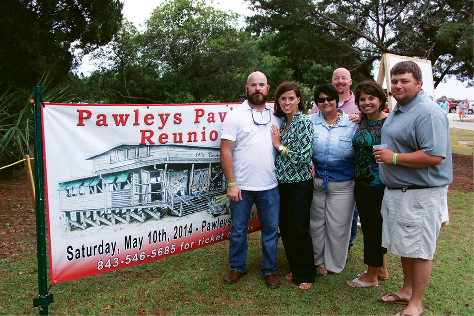 A group of friends share stories told by their parents and friends as they stand by an image of the original Pawleys Island Pavilion. Each year the reunion is held at the site where the pavilion stood prior to burning in 1970.