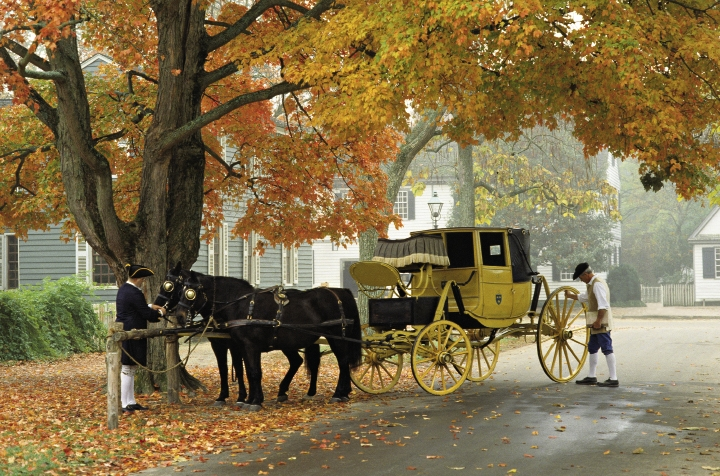 Virginia colonists drive horse-led carriages down Duke of Gloucester Street, the main thoroughfare in Colonial Williamsburg. Below: Kids try out Native American tools at Jamestown Settlement's Powhatan Indian Village.