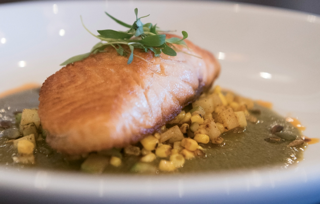 South Of The Border Salmon: LUNA's Salmon en Mole Verde drapes a filet over grilled sweet corn, chayote squash and pepitas.