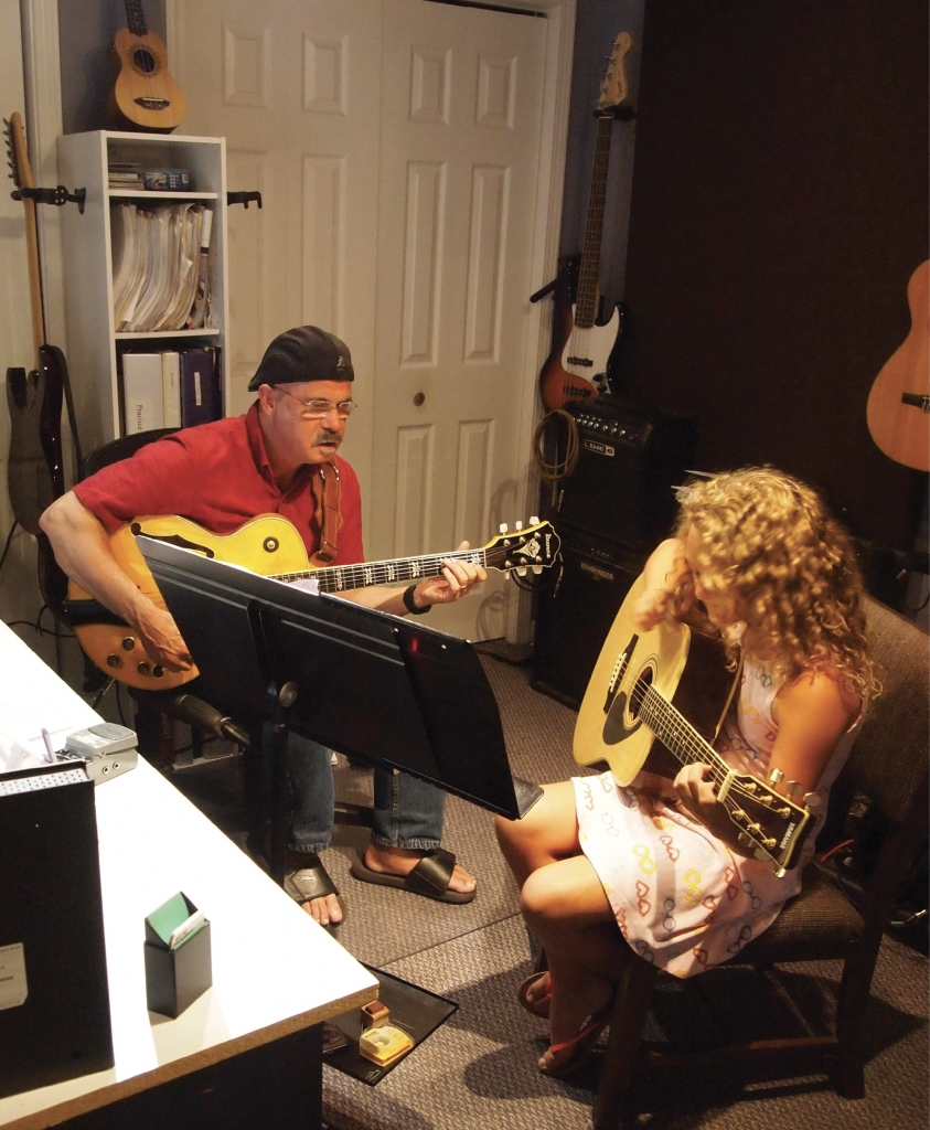 Fun at Any Age: Guitar instructor Wayne Cockfield teaches 10-year-old Lyla Bridges beginner guitar.