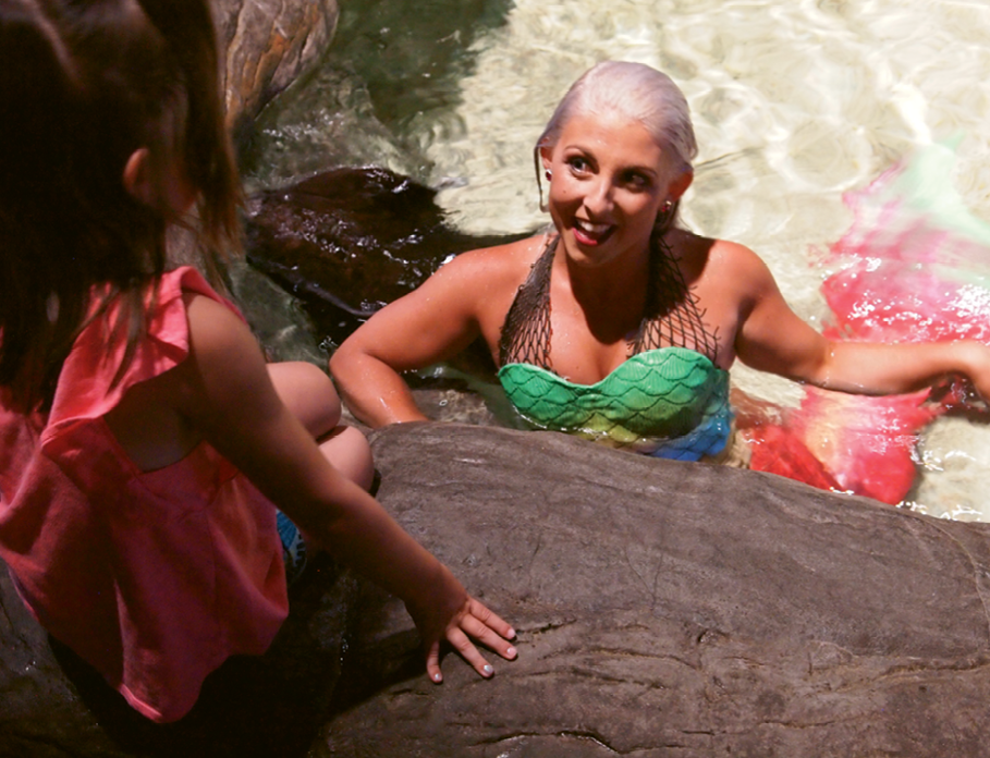 Alex McMinn, in full mermaid regalia, meets and poses for photographs with children in Ray Bay.