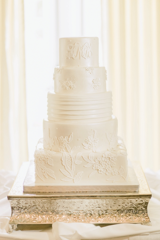 The Cake: Myra Ranta of Incredible Edibles replicated the flowers, lace and appliques on Hillary's dress. Hundreds of tiny sugar flowers and sugar appliques were created by hand. The cake was first frosted with buttercream, then it was covered with white fondant.